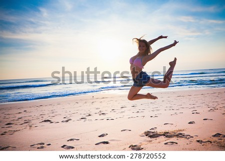 young girl dancing at the beach at blue sky background, summer vacation with joy