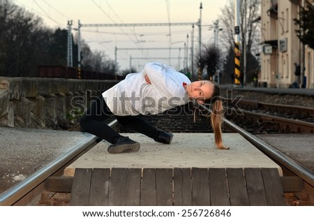 Young girl dancing on the train station - stock photo