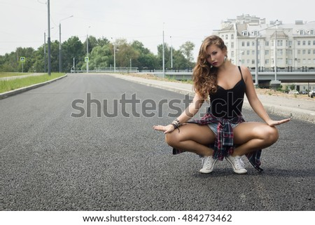 Young girl dancing regeton on a city street. Dancing and urban culture concept.