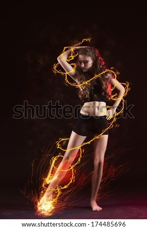 young girl dancing with fire stripes and ribbon in studio black backdrop