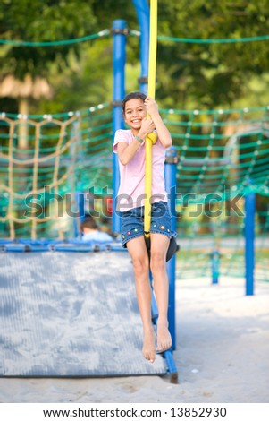Young girl dangling on playground swing - stock photo