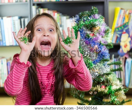 Young girl decorating Christmas tree making funny face - stock photo