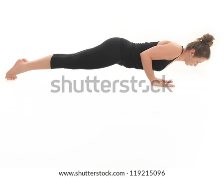 young girl demonstrating advanced yoga pose, full body view, dressed in blak, on white background - stock photo