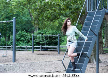 Young girl descending stairs at the park's playground - stock photo