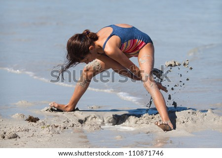 young girl digging a hole in the sand of a beach - stock photo