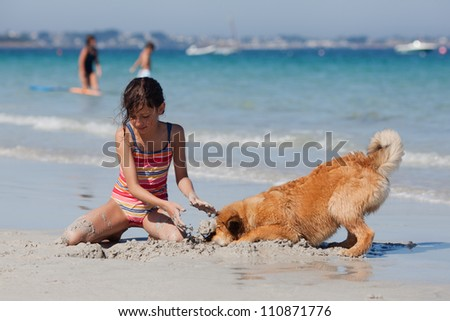 young girl digs a hole in the sand of a beach and hits her dog with the mud
