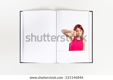 Young girl doing a bad signal printed on book - stock photo