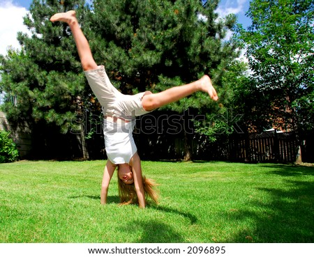 Young girl doing a cartwheel on green grass - stock photo