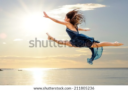 Young girl doing artistic graceful jump at sea side. - stock photo