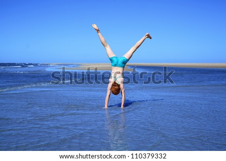 Young girl doing cartwheels on the beach - stock photo
