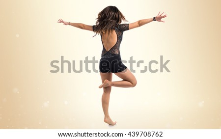 Young girl doing classical dance over ocher background