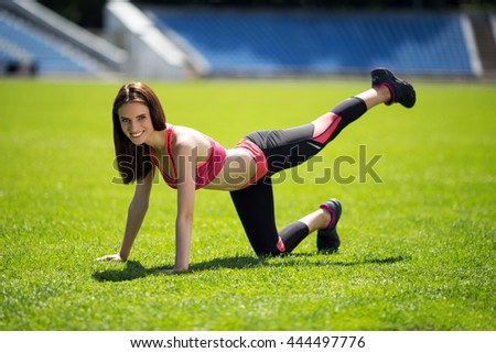 young girl  doing core workout at a stadium - stock photo