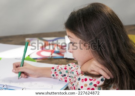 Young girl doing her homework on a wooden table - stock photo