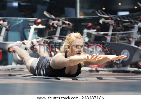 Young girl doing plank on her belly - stock photo