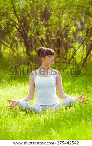 Young girl doing yoga on a green grass in summer