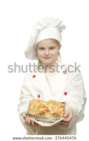 Young girl dressed as chef presenting fresh baked cake on white background. - stock photo