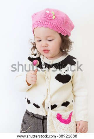 Young girl dressed fashionably for fall and enjoying a lollipop