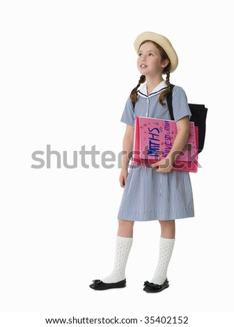 Young girl dressed in uniform holding school work - stock photo