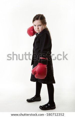 young girl dressed up as a business person wearing boxing gloves