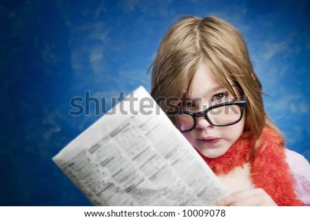 Young Girl Dressed Up in Reading Glasses Reading a Newspaper - stock photo
