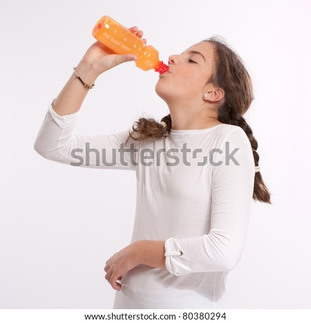 Young girl drinking an orange drink from a plastic bottle - stock photo