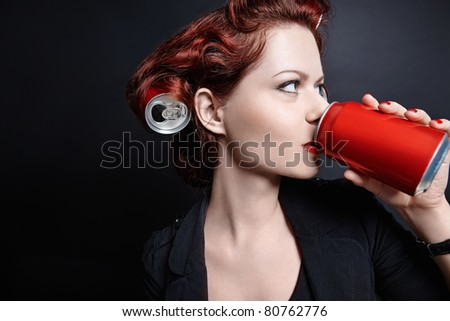 Young girl drinking from a can - stock photo