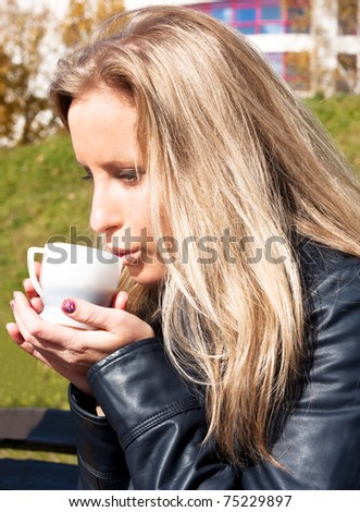 Young girl drinking hot tea in the park - stock photo