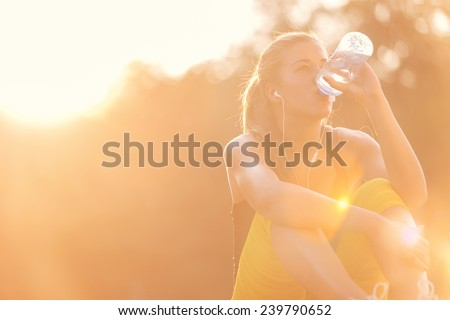 Young girl drinking water after workout - stock photo
