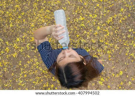Young girl drinking water during morning jogging. top view - stock photo