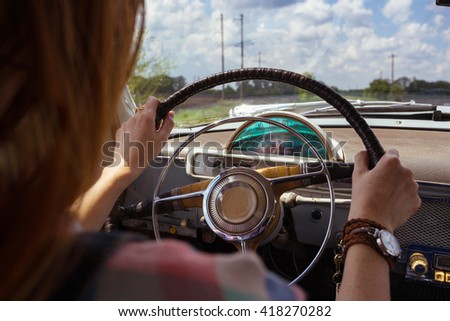 young girl driving a retro car by the road at the fields