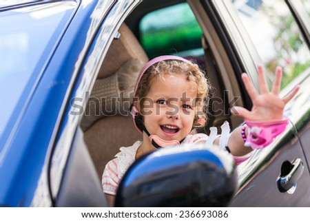 Young girl driving daddy's car - stock photo