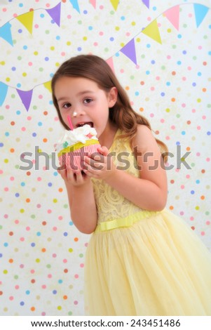 Young girl eating a birthday cake with cream on her nose - stock photo