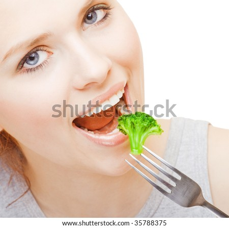 Young girl eating broccoli on white background - stock photo