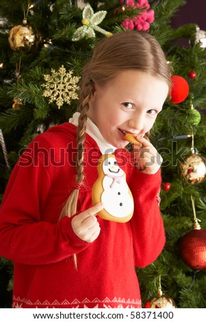 Young Girl Eating Cookie In Front Of Christmas Tree - stock photo