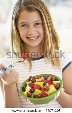 Young Girl Eating Fresh Fruit Salad - stock photo