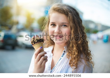 Young girl eating ice cream in the city street - stock photo