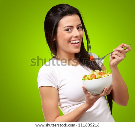Young Girl Eating Salad From Bowl Isolated On Green Background