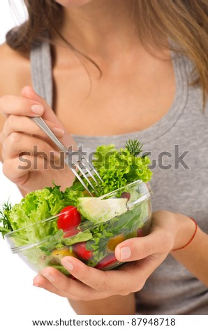 Young girl eating salad sitting on her bed at home