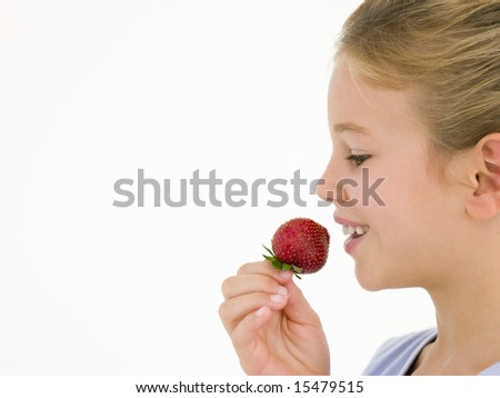 Young girl eating strawberry smiling - stock photo