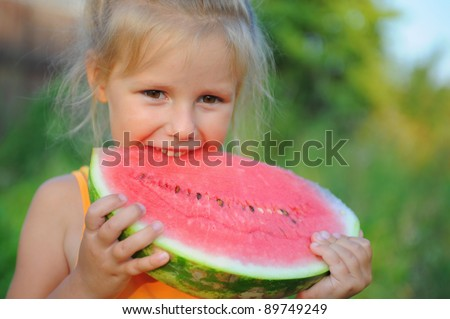 Young girl eating watermelon in the park