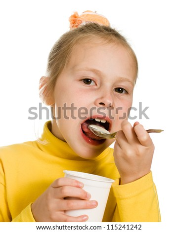 Young girl eating yogurt on a white background.