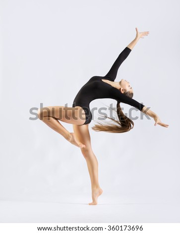 Young girl engaged art gymnastic on grey - stock photo