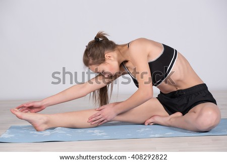 young girl engaged in yoga exercising and stretching
