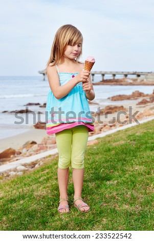 young girl enjoying ice cream at the beach on summer vacation - stock photo