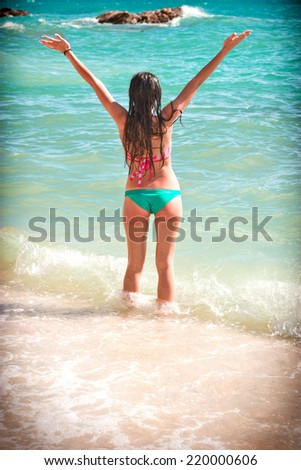Young girl enjoying the sun and in sea waves - stock photo