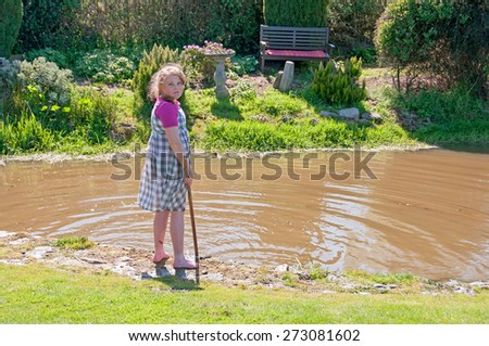 Young girl enjoying the sunshine & playing in the garden pond water