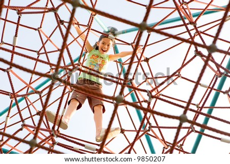 Young girl excited that she has reached the top of the giant climbing web activity. - stock photo
