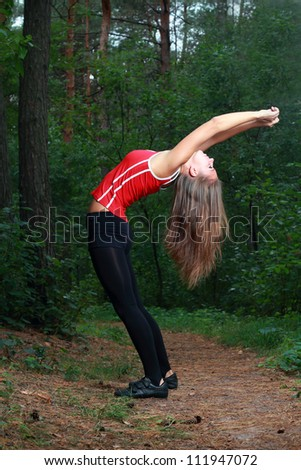 Young girl exercising in the park - stock photo