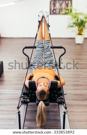 Young girl exercising on a reformer bed, close-up - stock photo