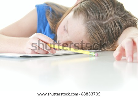 Young girl falling asleep during school work - stock photo